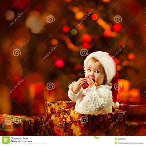 christmas baby  santa hat holding red ball  present
