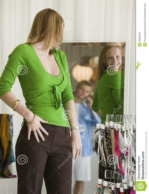 Woman Looking At Clothing In Store Mirror Stock Photo