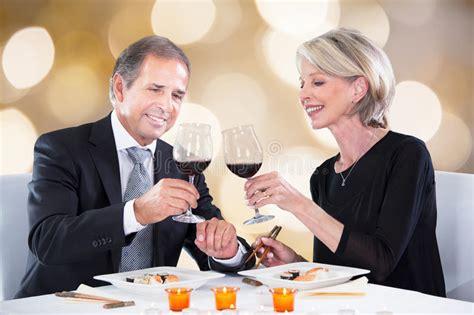 bicchieri ristorante coppie felici alla tostatura della tavola ristorante