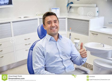 happy showing thumbs up at dental clinic stock photo