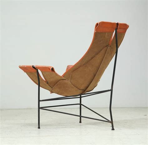 leathercrafter sling chair in brown leather on tri leg