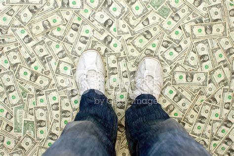 Man Standing On A Floor Of Dollar Bills Stock