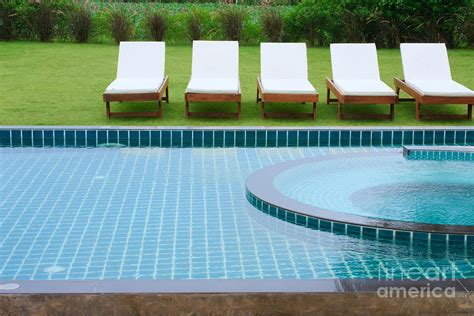 swimming pool and chairs by atiketta sangasaeng swimming