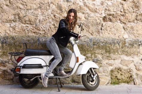 junge frau mit einem vintage motorrad spielen kostenlose