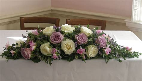 ceremony table flower arrangement  ivory avalanch roses