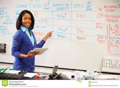 Science Teacher Standing At Whiteboard With Digital Tablet