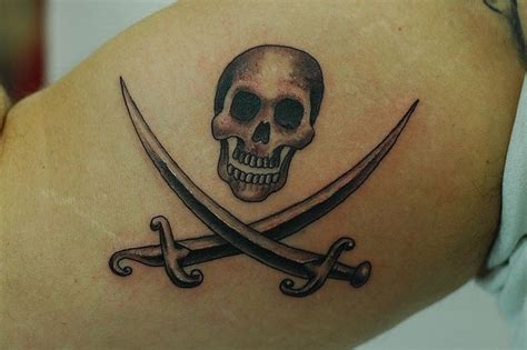 small grey jolly roger tattoo  biceps