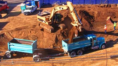 excavator fills dump trucks  dirt  construction site youtube