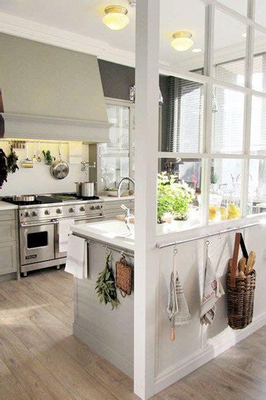 une cuisine blanche semi ouverte avec une verri 232 re interieure