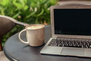 Large, White, Coffee, Cup, Near, A, Laptop, On, A, Desk, At, The, Green, Plant, Background, Stock, Photo