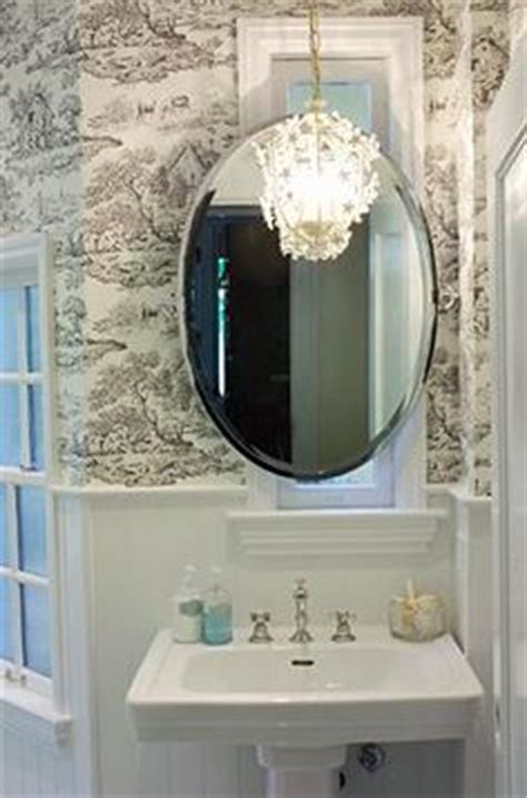 black oval bathroom mirror high contrast powder room walls white beadboard 17412