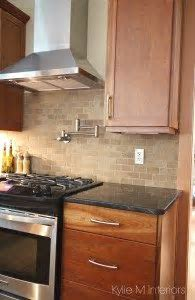 Natural cherry cabinets, travertine tile backsplash, black