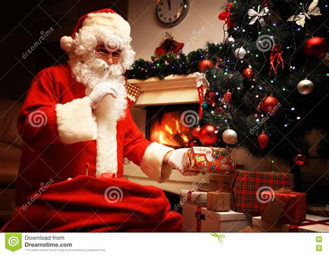 Santa Claus Putting Gift Box Or Present Under Christmas