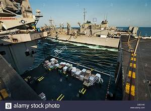 Sailors Remove Cargo From An Aircraft Elevator During A