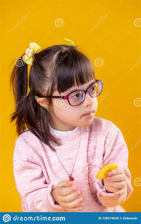 Dark Haired Girl With Down Syndrome Carrying Orange Chips