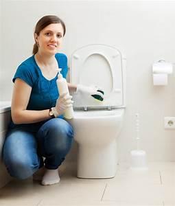 toilette de nettoyage de jeune femme dans la salle de With toilette dans la salle de bain