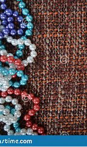Pearl Necklace On The Brown Fabric Background Texture ...