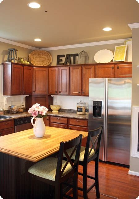 Decorating Ideas For On Top Of Kitchen Cabinets by How To Decorate Above Kitchen Cabinets From Thrifty Decor