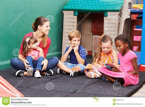 of children reading book in preschool stock photo 719 | group children reading book preschool nursery teacher 52052716