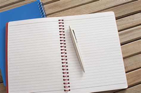 Image Of Pen On Open Spiral Notebook On Top Of Wooden Table Freebiephotography