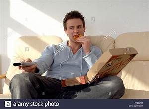 man sitting on a sofa eating pizza and watching television ...