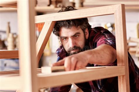 artisan furniture designer sanding  chair   workshop