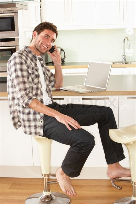 young man relaxing sitting  kitchen stock image