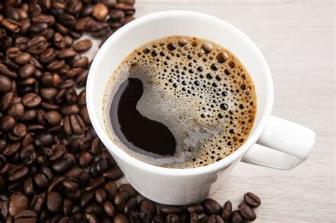 Try ethiopia yirgacheffe from fry coffee composition: White Cup Of Coffee With Foam Against A Background Of Fried Coffee Beans Close Up Stock Photo ...