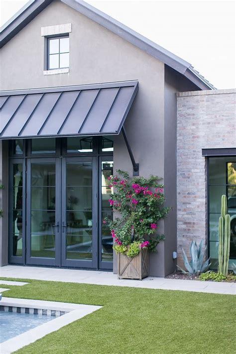 exterior grey stucco brick metal roof black steel doors windows exterior bric