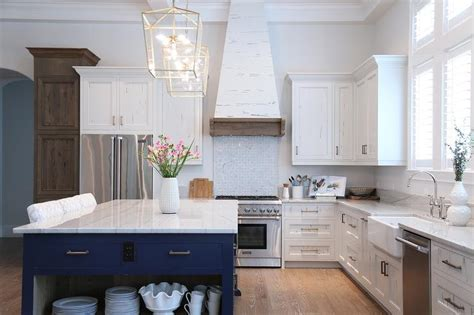 kitchen island with cooktop and seating white and navy blue kitchen with white pecky cypress range
