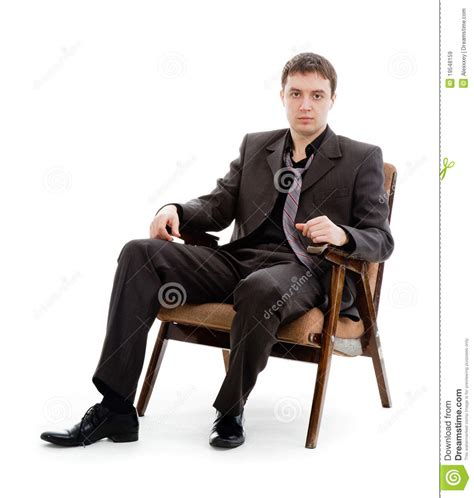 a in a suit and tie sitting in a chair royalty