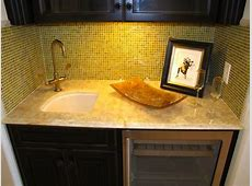 A small wetbar area with granite countertop and tiled
