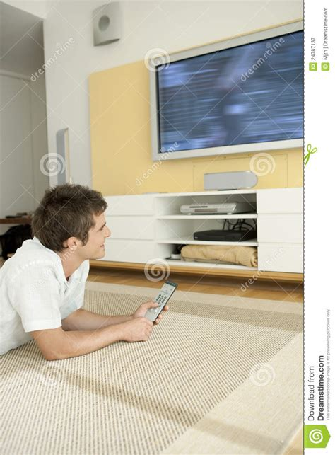 man laying   floor watching tv royalty  stock