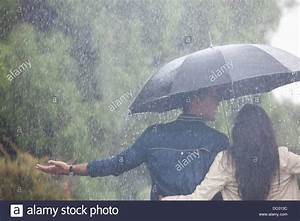 Couple walking with arms outstretched under umbrella in ...