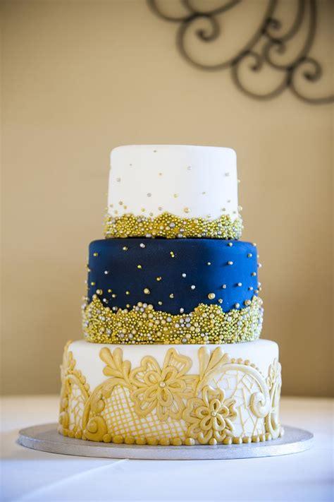 intricate designs  tiered navy gold  white wedding
