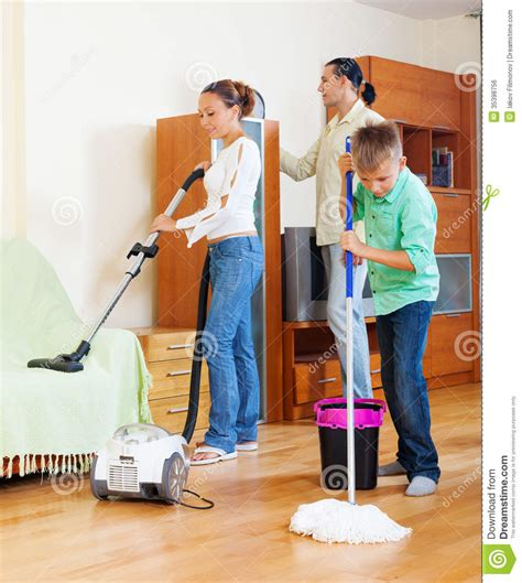 Clean The Living Room In by Family With Boy Cleaning In Living Room Stock