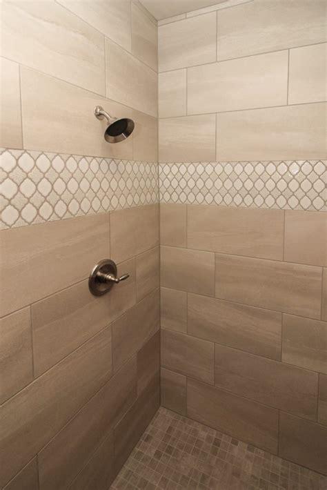 beige tiled shower  accent tile strip bathroom wall