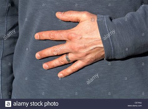 man s hand wearing silver wedding ring on finger stock
