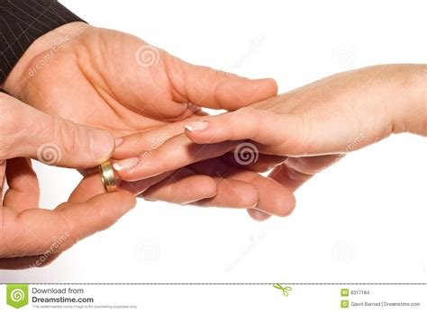 man putting wedding ring on bride s finger stock images