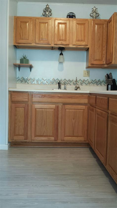 tile flooring with oak cabinets honey oak kitchen cabinets with gray pergo willow lake pine floors and herringbone tile