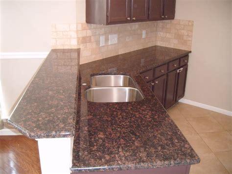 brown granite countertops with subway tile backsplash