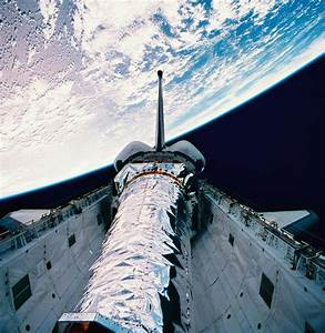 The Space Shuttle With Its Open Cargo Bay Orbiting Above ...
