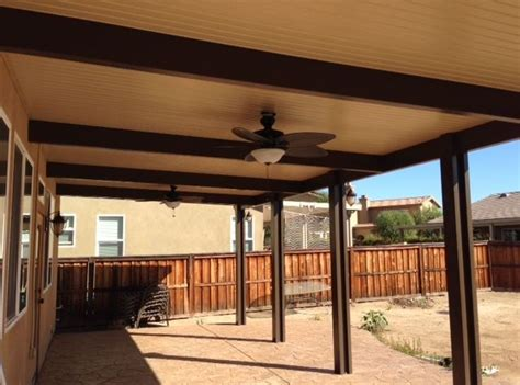 faux wood beams give a touch to aluminum patio covers