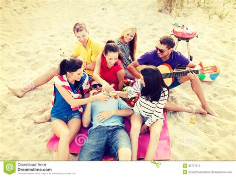 Group Of Friends With Guitar Having Fun On Beach Stock