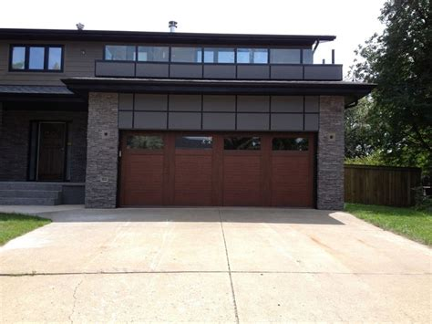 Modern Garages Photo Gallery by A Stained Steel Garage Door Adds Warmth To This