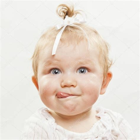 Adorable Baby Girl With Tongue Sticking Out Stock Photo