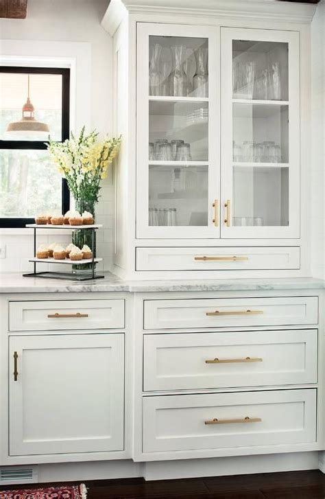 Our shaker white kitchen cabinet line combines the sleek lines you love with an elegant white finish to create a one of a kind kitchen design. A glass front china cabinet accented with brass pulls is ...