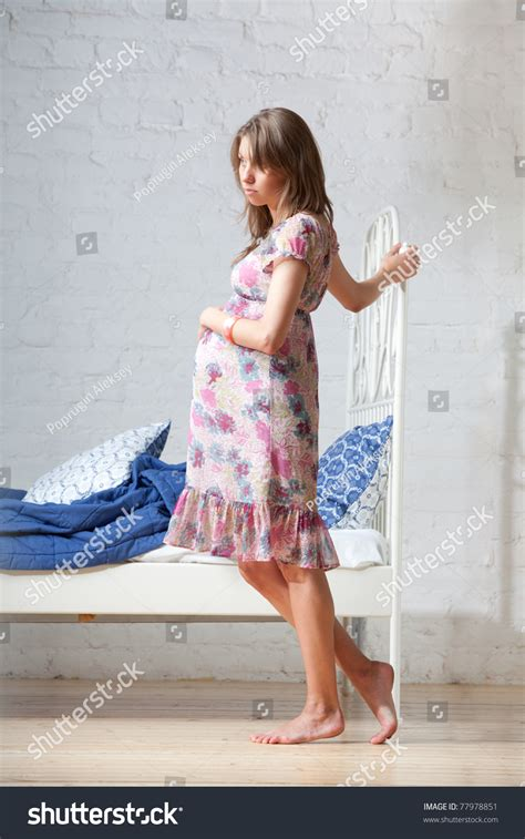 young pregnant woman standing   bed stock photo