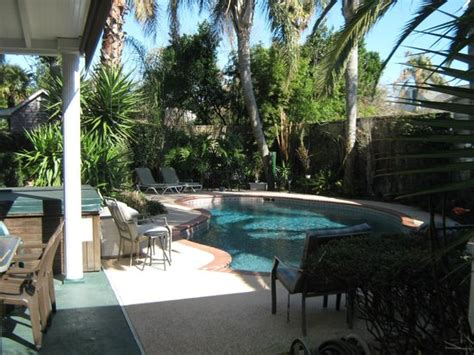 lovely yard has tub pool garden pond bar and patio