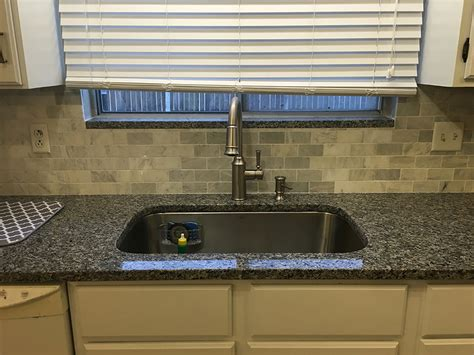 caledonia granite with backsplash tiles